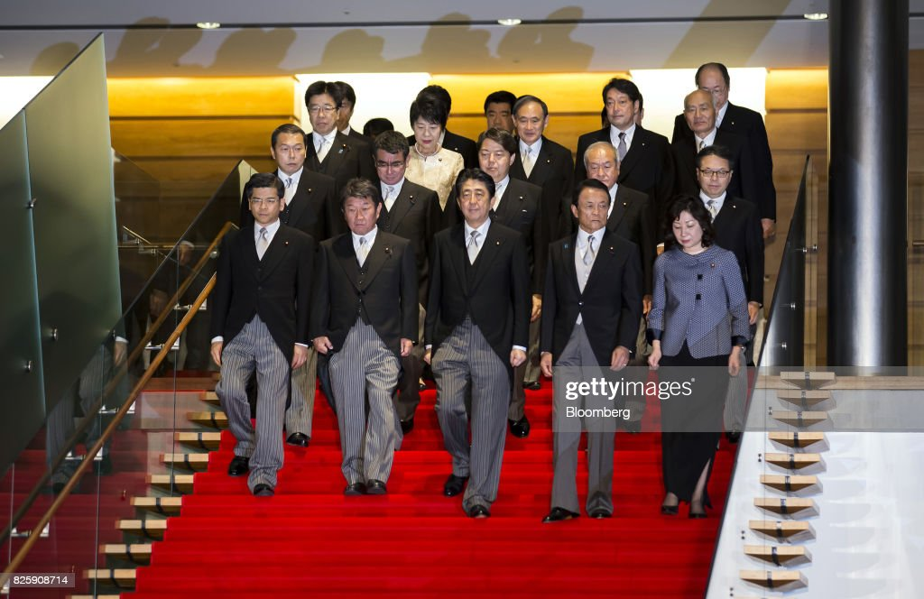 Shinzo Abe, Japan's prime minister, front row center, walks to a group photograph with his new cabinet members at the Prime Minister's official residence in Tokyo, Japan, on Thursday, Aug. 3, 2017. Abe reshuffled his ministers and party officials after a slump in popularity and a humiliating local election defeat. Photographer: Tomohiro Ohsumi/Bloomberg via Getty Images