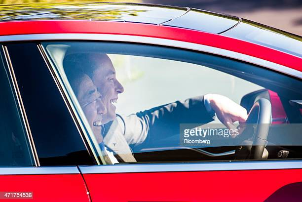 Shinzo Abe Japan's prime minister left and Elon Musk cofounder and chief executive officer of Tesla Motors Inc share a laugh as they test drive a...