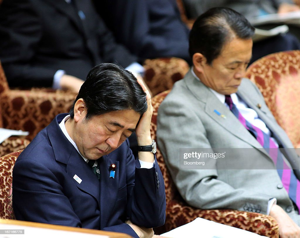 Shinzo Abe, Japan's prime minister, left, and Taro Aso, Japan's deputy prime minister and finance minister, attend a budget committee session at the upper house of parliament in Tokyo, Japan, on Wednesday, Feb. 20, 2013. Abe said that the need to buy foreign bonds has decreased, backing away from a policy proposal that may be seen by other nations as a direct attempt to weaken the yen. Photographer: Haruyoshi Yamaguchi/Bloomberg via Getty Images