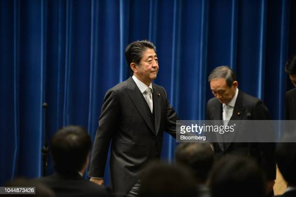Shinzo Abe Japan's prime minister left leaves a news conference as Yoshihide Suga chief cabinet secretary bows at the Prime Minister's official...