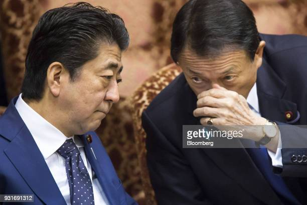 Shinzo Abe, Japan's prime minister, left, listens to Taro Aso, Japan's deputy prime minister and finance minister, during a budget committee session...