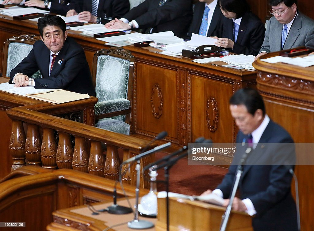 Shinzo Abe, Japan's prime minister, left, looks on as Taro Aso, Japan's deputy prime minister and finance minister, delivers his policy speech at the lower house of Parliament in Tokyo, Japan, on Thursday, Feb. 28, 2013. Aso said Japan's fiscal state is very grim, and the government can't provide fiscal stimulus perpetually. Photographer: Haruyoshi Yamaguchi/Bloomberg via Getty Images