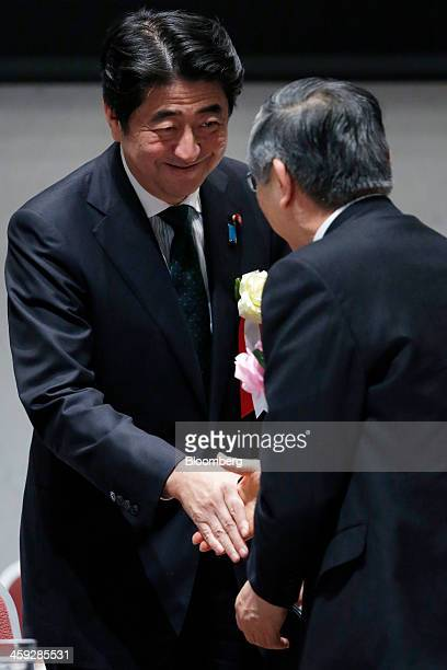 Shinzo Abe Japan's prime minister left shakes hands with Haruhiko Kuroda governor of the Bank of Japan as he leaves a meeting at the business lobby...