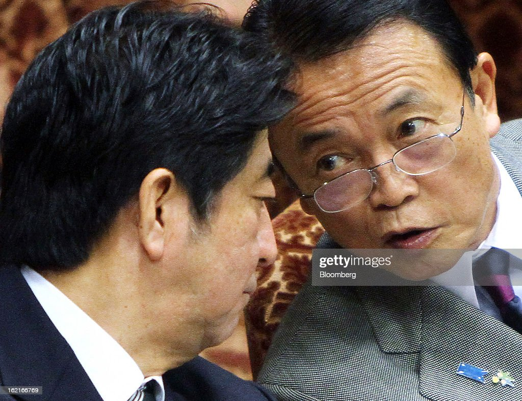 Shinzo Abe, Japan's prime minister, left, speaks to Taro Aso, Japan's deputy prime minister and finance minister, during a budget committee session at the upper house of the parliament in Tokyo, Japan, on Wednesday, Feb. 20, 2013. Abe said that the need to buy foreign bonds has decreased, backing away from a policy proposal that may be seen by other nations as a direct attempt to weaken the yen. Photographer: Haruyoshi Yamaguchi/Bloomberg via Getty Images