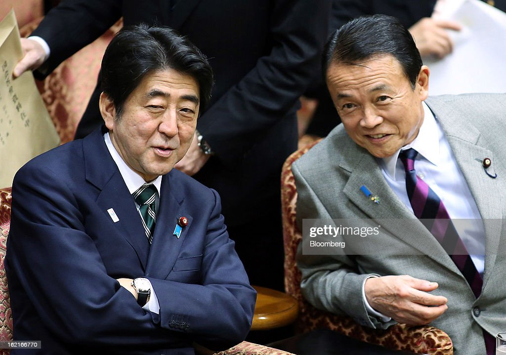 Shinzo Abe, Japan's prime minister, left, speaks to Taro Aso, Japan's deputy prime minister and finance minister, during a budget committee session at the upper house of parliament in Tokyo, Japan, on Wednesday, Feb. 20, 2013. Abe said that the need to buy foreign bonds has decreased, backing away from a policy proposal that may be seen by other nations as a direct attempt to weaken the yen. Photographer: Haruyoshi Yamaguchi/Bloomberg via Getty Images