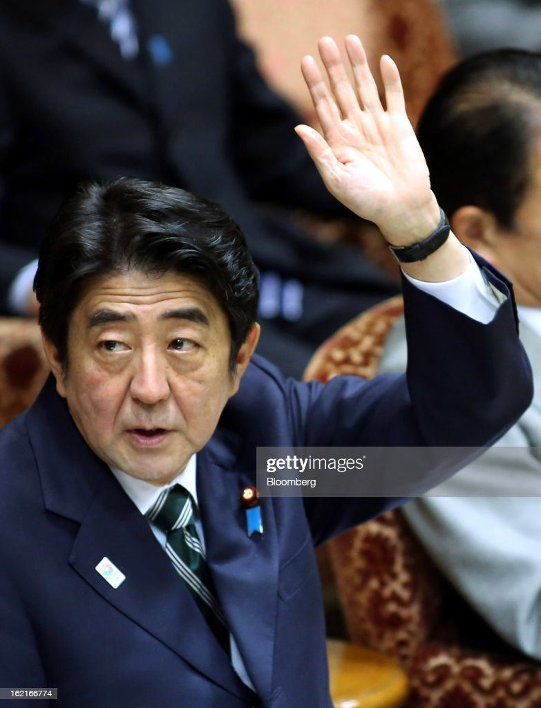 Shinzo Abe, Japan's prime minister, raises his hand to answer a question during a budget committee session at the upper house of parliament in Tokyo, Japan, on Wednesday, Feb. 20, 2013. Abe said that the need to buy foreign bonds has decreased, backing away from a policy proposal that may be seen by other nations as a direct attempt to weaken the yen. Photographer: Haruyoshi Yamaguchi/Bloomberg via Getty Images