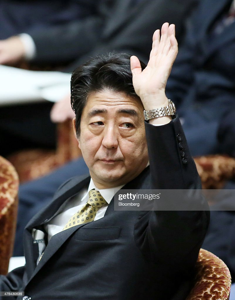 Shinzo Abe, Japan's prime minister, raises his hand to speak during a budget committee session in the lower house of the Parliament in Tokyo, Japan, on Friday, Feb. 28, 2014. Abe's ruling Liberal Democratic Party is planning a governance code for Japanese companies to boost their competitiveness and enhance investor protection, an official said. Photographer: Haruyoshi Yamaguchi/Bloomberg via Getty Images