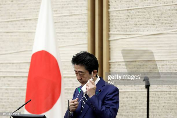 Shinzo Abe, Japan's prime minister, removes a protective mask before speaking during a news conference at the prime minister's official residence on...
