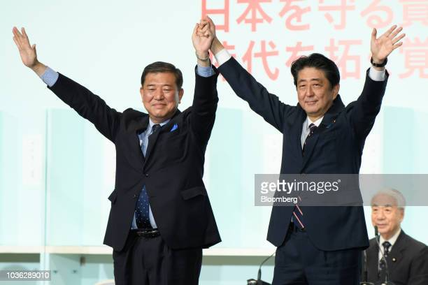 Shinzo Abe Japan's prime minister right and Shigeru Ishiba former defense minister raise their arms in victory after Abe was elected president of the...