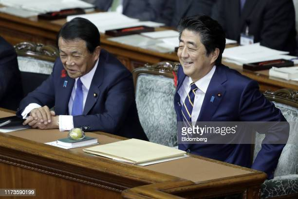 Shinzo Abe, Japan's prime minister, right, and Taro Aso, deputy prime minister and finance minister, react during an extraordinary session at the...