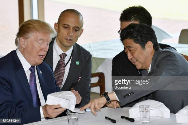 Shinzo Abe Japan's prime minister right gestures towards a hat as US President Donald Trump left speaks at Kasumigaseki Country Club in Kawagoe...