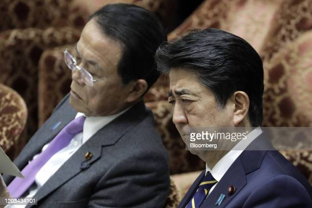 Shinzo Abe, Japan's prime minister, right, reacts as Taro Aso, deputy prime minister and finance minister, sits during a budget committee session at...