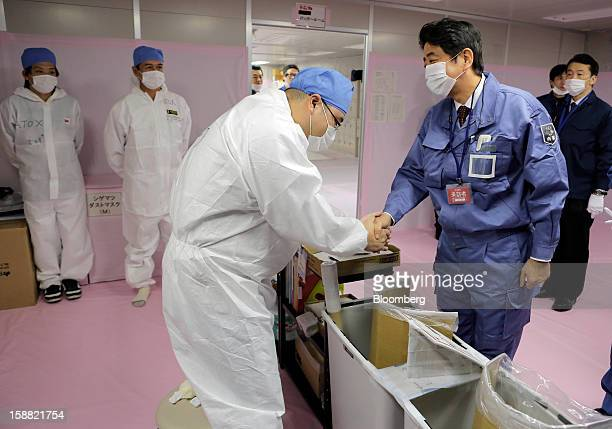 Shinzo Abe Japan's prime minister right shakes hands with a worker inside the emergency operations center at Tokyo Electric Power Co's Fukushima...
