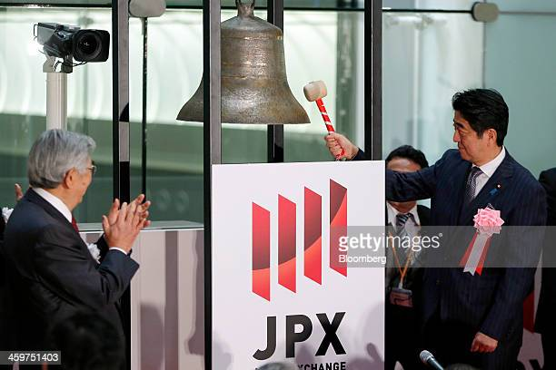 Shinzo Abe Japan's prime minister right strikes a bell as Atsushi Saito chief executive officer of Japan Exchange Group Inc left applauds during a...