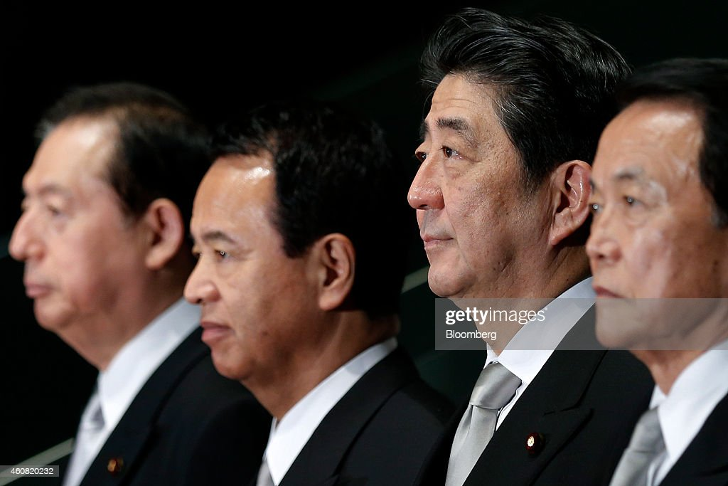 Shinzo Abe, Japan's prime minister, second from right, poses for a group photograph with members of his new cabinet including Akihiro Ohta, re-appointed land, infrastructure, and transport minister, left, Akira Amari, re-appointed economic revitalization minister, second from left, Taro Aso, re-appointed deputy prime minister and minister for finance and financial services, right, at the prime minister's official residence in Tokyo, Japan, on Wednesday, Dec. 24, 2014. Abe appointed a former soldier and security veteran as his new defense minister, as he prepares to push through legislation to toughen the countrys military stance amid a dispute with China. Photographer: Kiyoshi Ota/Bloomberg via Getty Images