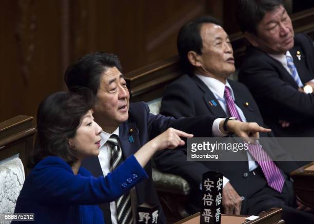 Shinzo Abe Japan's prime minister second left and Seiko Noda Japan's internal affairs and communications minister left gesture during a plenary...