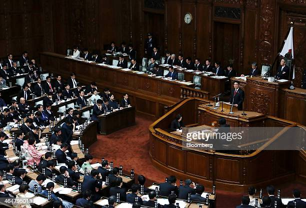 Shinzo Abe Japan's prime minister standing at podium delivers his policy speech during a session in the lower house of Parliament in Tokyo Japan on...