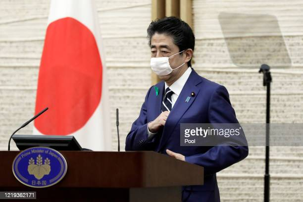 Shinzo Abe, Japan's prime minister, wearing a protective mask, arrives for a news conference at the prime minister's official residence on April 17,...