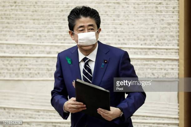 Shinzo Abe, Japan's prime minister, wearing a protective mask, leaves a news conference at the prime minister's official residence on April 17, 2020...