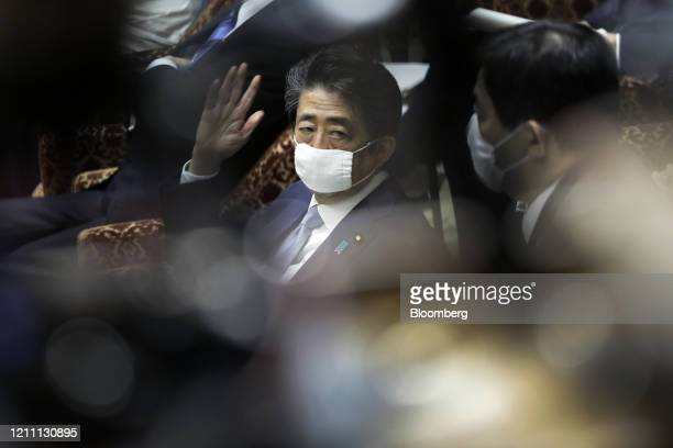 Shinzo Abe, Japan's prime minister, wears a protective mask as he gestures to speak during a budget committee session at the lower house of...