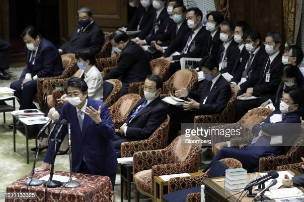 Shinzo Abe, Japan's prime minister, wears a protective mask as speaks during a budget committee session at the lower house of parliament in Tokyo,...