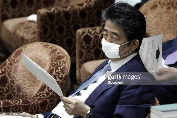 Shinzo Abe, Japan's prime minister, wears a protective mask during a budget committee session at the lower house of parliament in Tokyo, Japan, on...