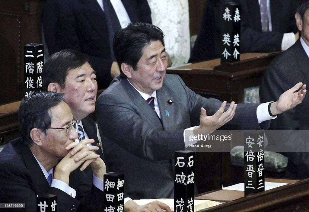 Shinzo Abe, president of the Liberal Democratic Party (LDP), center right, speaks to Shigeru Ishiba, secretary general of the party, center left, before being elected Japan's prime minister at the lower house of parliament in Tokyo, Japan, on Wednesday, Dec. 26, 2012. Japan's lower house confirmed Abe as the nation's seventh prime minister in six years, returning him to the office he left in 2007 after his party regained power in a landslide election victory last week. Photographer: Haruyoshi Yamaguchi/Bloomberg via Getty Images