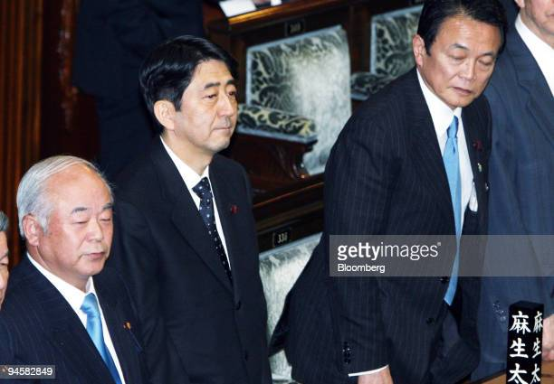 Shinzo Abe prime minister of Japan center Taro Aso foreign minister right and Fumio Kyuma defense minister left attends during a plenary session of...