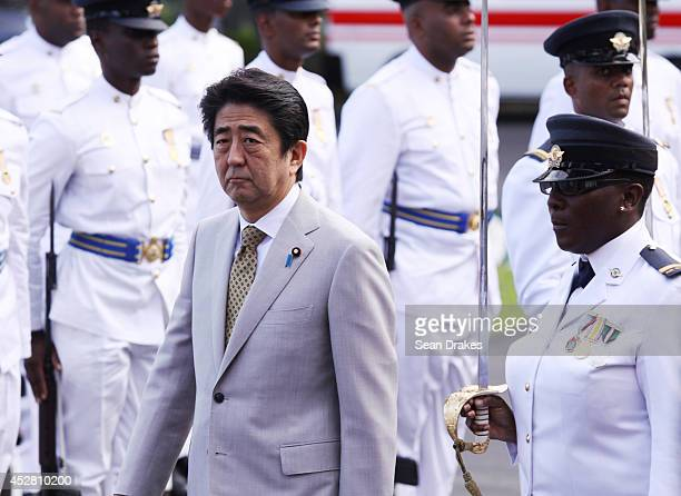 Shinzo Abe Prime Minister of Japan inspects the Trinidad and Tobago Air Guard at the Diplomatic Center on July 27 2014 in Port of Spain Trinidad...