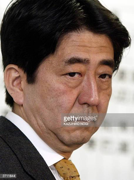 Shinzo Abe secretary general of the Liberal Democratic Party looks at a TV monitor reporting a vote counting in the general election for the House of...
