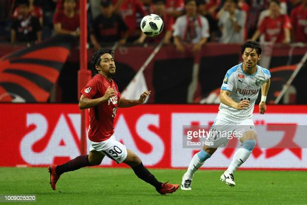 Shinzo Koroki of Urawa Red Diamonds and Akihiro Ienaga of Kawasaki Frontale compete for the ball during the JLeague J1 match between Urawa Red...