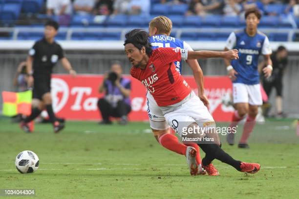 Shinzo Koroki of Urawa Red Diamonds and Ryosuke Yamanaka of Yokohama F.Marinos compete for the ball during the J.League J1 match between Yokohama...