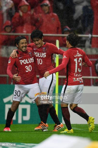 Shinzo Koroki of Urawa Red Diamonds celebrates scoring his side's third goal with his team mates Yosuke Kashiwagi and Toshiyuki Takagi during the...