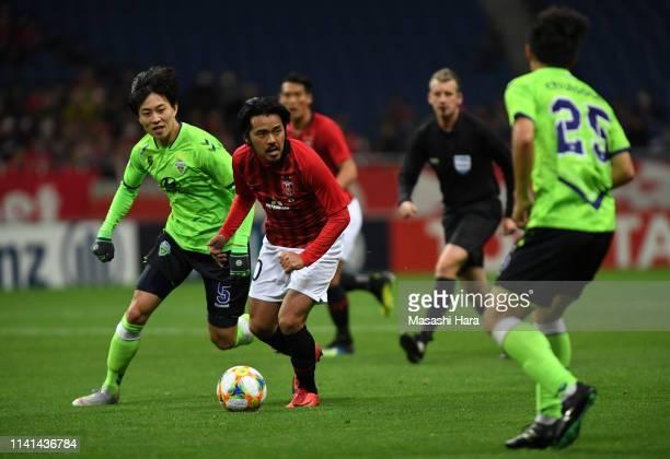 Shinzo Koroki of Urawa Red Diamonds controls the ball under pressure of Jeonbuk Hyundai Motors defense during the AFC Champions League Group G match...