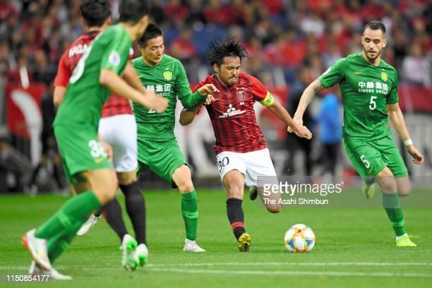Shinzo Koroki of Urawa Red Diamonds controls the ball under pressure of Beijing Guoan defense during the AFC Champions League Group G match between...