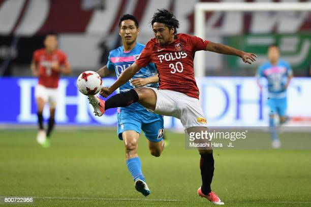 Shinzo Koroki of Urawa Red Diamonds controls the ball under pressure of Riki Harakawa of Sagan Tosu during the JLeague J1 match between Sagan Tosu...