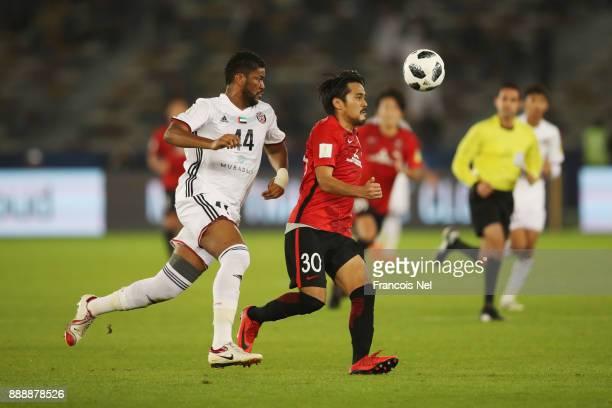 Shinzo Koroki of Urawa Red Diamonds is challenged by Fares Juma of AlJazira during the FIFA Club World Cup match between Al Jazira and Urawa Red...