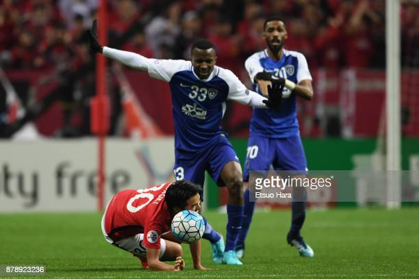 Shinzo Koroki of Urawa Red Diamonds is challenged by Osama Hawsawi of AlHilal during the AFC Champions League Final second leg match between Urawa...