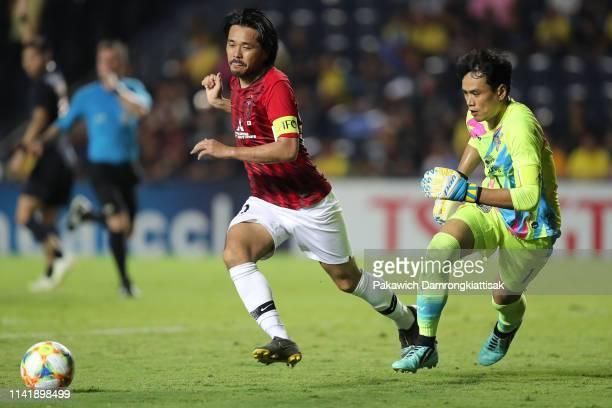 Shinzo Koroki of Urawa Red Diamonds kicks the ball past Siwarak Tedsungnoen of Buriram United during the AFC Champions League Group G match between...