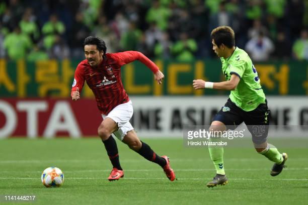 Shinzo Koroki of Urawa Red Diamonds runs past Kim Minhyeok of Jeonbuk Hyundai Motors during the AFC Champions League Group G match between Urawa Red...