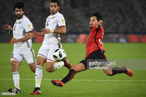Shinzo Koroki of Urawa Reds crosses the ball under the pressure from Mohamed Ayed and Salem Al Eedi of Al Jazira on December 9 2017 in Abu Dhabi...