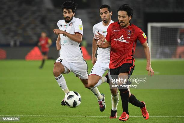 Shinzo Koroki of Urawa Reds dribbles the ball under the pressure from Mohamed Ayed and Salem Al Eedi of Al Jazira on December 9 2017 in Abu Dhabi...