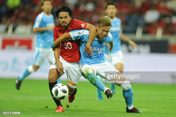Shinzo Koroki#30 of Urawa Red Diamonds and Yoshito Okubo#22 of Jubilo Iwata compete for the ball during the JLeague J1 match between Urawa Red...