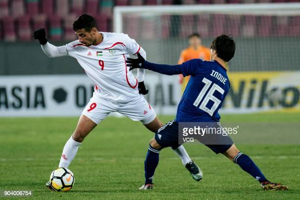 Shion Inoue of Japan and Oday Dabbagh of Palestine compete for the ball during the AFC U23 Championship Group B match between Japan and Palestine at...
