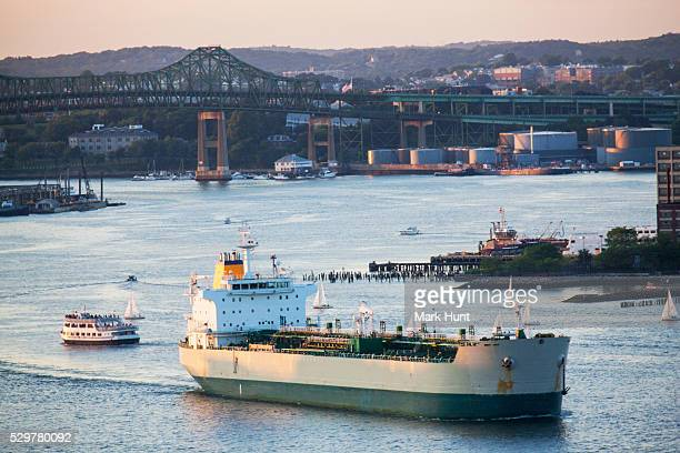 ship and boats in a river with a bridge in the background, tobin bridge, chelsea, boston, massachusetts, usa - massachusetts stock-fotos und bilder