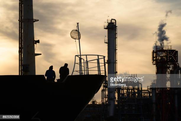 A ship and crew members are silhouetted as they travel past a plant at dusk in the Keihin industrial area of Kawasaki Kanagawa Prefecture Japan on...