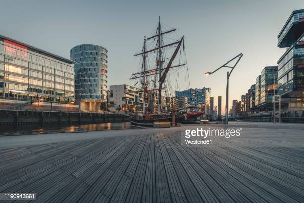 ship at harbor against sky in hafencity during sunset, hamburg, germany - amburgo foto e immagini stock