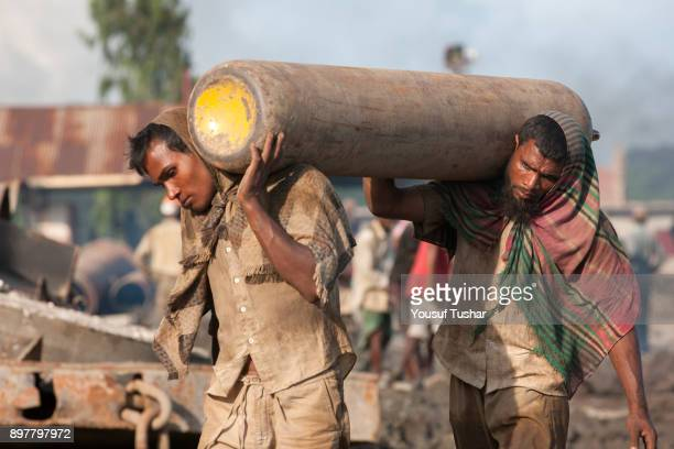 Ship breaking laborers carrying a gas tank at Sitakundo ship breaking yard. The ship breaking industry at Sitakundo started its operation in 1960.Due...
