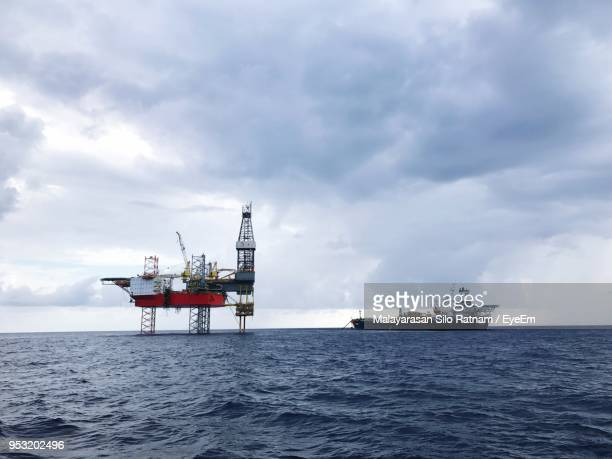 ship by oil rig in sea against sky - construction platform stock photos and pictures