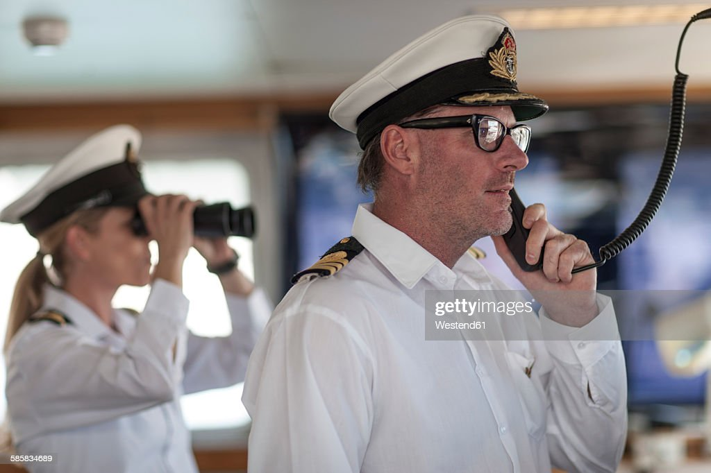 Ship captain on bridge talking on radio : Stock Photo